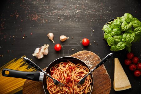 top view of tasty bolognese pasta in frying pan near ingredients and cutlery on black wooden background