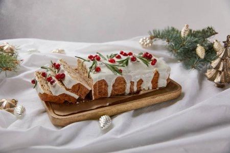 Photo pour Gâteau de Noël traditionnel avec canneberge sur panneau en bois près de boules d'argent et aiguilles de pin isolées sur gris - image libre de droit