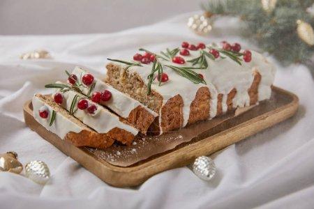 Photo pour Gâteau de Noël traditionnel avec canneberge sur panneau en bois près de boules d'argent et aiguilles de pin isolées sur gris avec neige tombante - image libre de droit