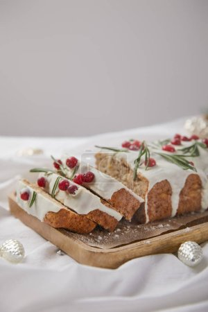 Photo for Traditional Christmas cake with cranberry on wooden board near silver baubles isolated on grey - Royalty Free Image