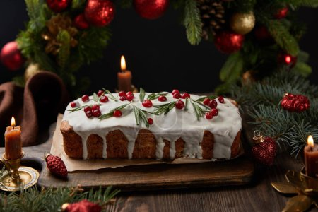 traditional Christmas cake with cranberry near Christmas wreath with baubles and candles on wooden table isolated on black