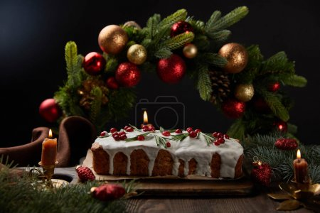 Photo pour Foyer sélectif de gâteau de Noël traditionnel avec canneberge près de couronne de Noël avec des boules sur table en bois isolé sur noir - image libre de droit