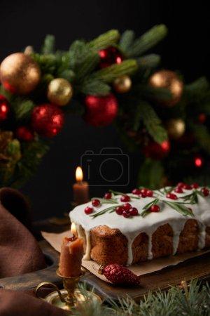 Photo pour Foyer sélectif de gâteau de Noël traditionnel avec canneberge près de couronne de Noël avec des boules et des bougies brûlantes sur table en bois isolé sur noir - image libre de droit