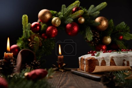 Photo for Traditional Christmas cake with cranberry near Christmas wreath with baubles and burning candles on wooden table isolated on black - Royalty Free Image