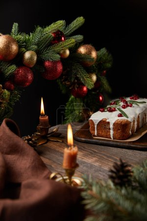 Photo for Selective focus of traditional Christmas cake with cranberry near Christmas wreath with baubles and burning candles on wooden table isolated on black - Royalty Free Image