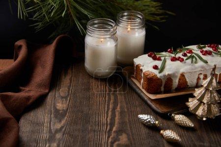 Photo pour Gâteau de Noël traditionnel avec canneberge près des bougies, serviette, boules et pin sur table en bois - image libre de droit