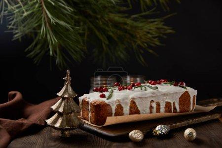 Photo pour Gâteau de Noël traditionnel à la canneberge près du pin, baies et bougies sur table en bois - image libre de droit