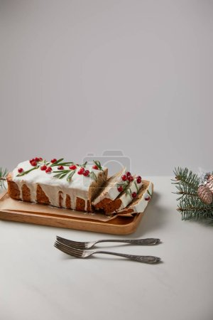 Photo pour Traditional Christmas cake with cranberry near forks, baubles and pine on white table isolated on grey - image libre de droit