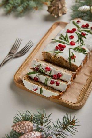 Photo pour Gâteau de Noël traditionnel avec canneberge près des fourchettes, baubles et pin sur table blanche - image libre de droit