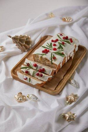 Photo pour Gâteau de Noël traditionnel avec canneberge sur carton en bois près de baubles sur tissu blanc isolé sur gris - image libre de droit