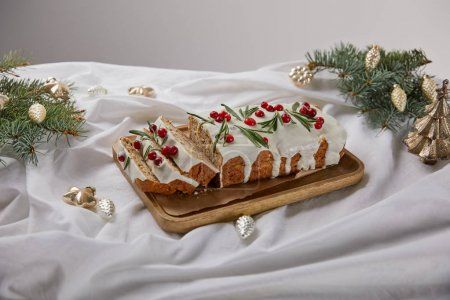 Photo pour Traditional Christmas cake with cranberry on wooden board near silver baubles and pine isolated on grey - image libre de droit