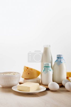 Photo for Various fresh organic dairy products and eggs on wooden table isolated on white - Royalty Free Image