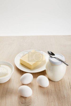 Photo pour Délicieux produits laitiers biologiques et oeufs sur table en bois isolés sur - image libre de droit