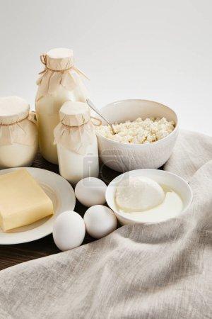 Photo pour Délicieux produits laitiers frais et oeufs sur table en bois avec tissu isolé sur blanc - image libre de droit