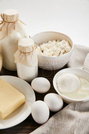 Photo pour Délicieux produits laitiers frais et oeufs sur table rustique en bois avec tissu isolé sur blanc - image libre de droit