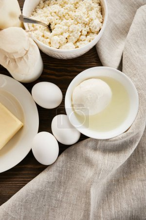 Photo for Top view of delicious fresh dairy products and eggs on rustic wooden table with cloth - Royalty Free Image