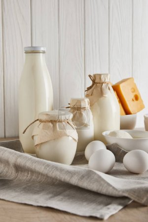Photo for Delicious fresh dairy products and eggs on white wooden background - Royalty Free Image