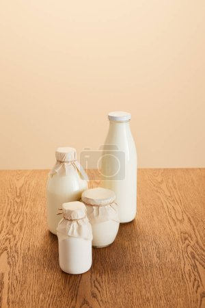 Photo for Tasty organic dairy products in bottles on rustic wooden table isolated on beige - Royalty Free Image