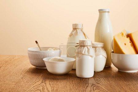 Photo pour Produits laitiers biologiques savoureux sur table en bois rustique isolée sur beige - image libre de droit