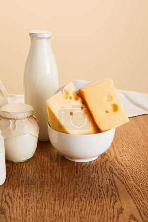 Photo for Tasty organic dairy products on rustic wooden table isolated on beige - Royalty Free Image