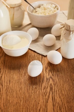Photo pour Orientation sélective de divers produits laitiers et œufs biologiques frais sur une table en bois rustique - image libre de droit