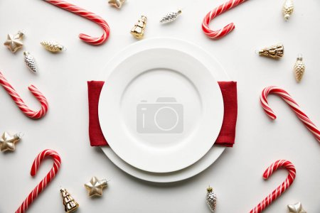Photo for Top view of festive Christmas table setting on white background with decoration and candies - Royalty Free Image
