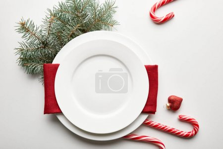 Photo for Top view of festive Christmas table setting on white background with pine branch and candies - Royalty Free Image