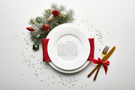 Foto de Top view of festive Christmas table setting on white background with decorated pine branch and confetti - Imagen libre de derechos