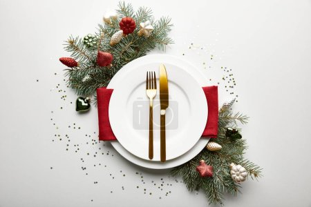 Photo pour Top view of festive Christmas table setting on white background with decorated pine branch and confetti - image libre de droit