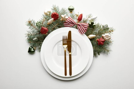 Photo pour Top view of white plates with cutlery near festive Christmas tree branch with baubles on white background - image libre de droit