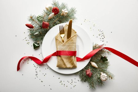 Photo for Top view of white plate with napkin, cutlery and ribbon near festive Christmas tree branch with baubles and confetti on white background - Royalty Free Image