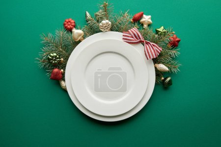 Photo for Top view of white plates near festive Christmas tree branch with baubles on green background - Royalty Free Image
