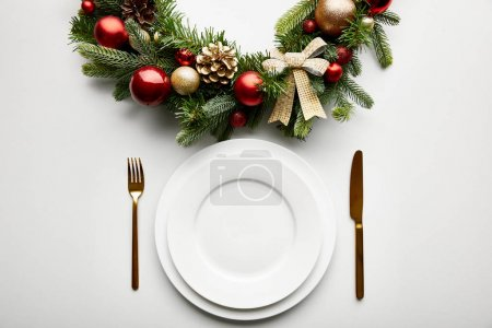 Foto de Top view of white plates with golden cutlery near festive Christmas wreath with baubles on white background - Imagen libre de derechos