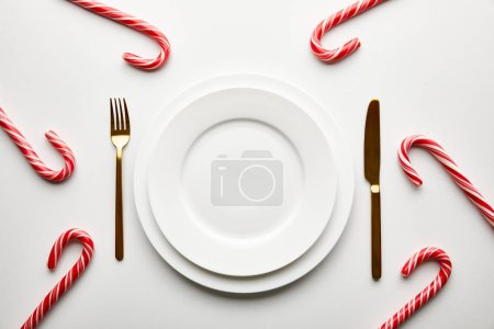 Photo for Top view of festive Christmas table setting on white background with candies - Royalty Free Image