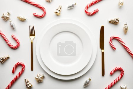Photo for Top view of Christmas table setting on white background with festive decoration and candies - Royalty Free Image