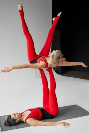 Photo pour Young women practicing acroyoga on yoga mat in studio - image libre de droit