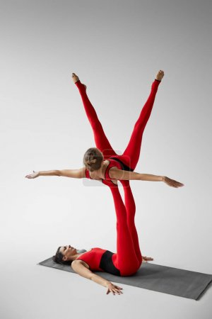 Photo pour Two women practicing acroyoga on yoga mat in studio isolated on grey - image libre de droit