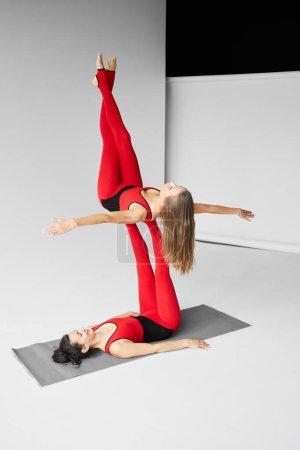 Photo pour Two girls practicing acroyoga on yoga mat - image libre de droit