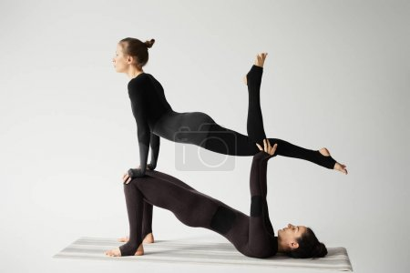Photo pour Young women practicing acroyoga on yoga mat isolated on grey - image libre de droit