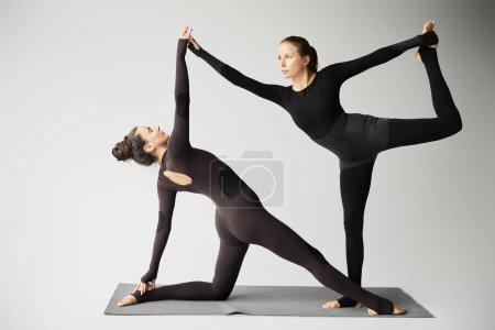Photo pour European women practicing acroyoga on yoga mat isolated on grey - image libre de droit