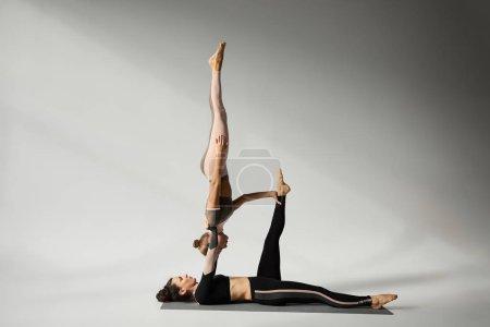 Photo pour Jeunes filles pratiquant l'acroyoga sur tapis de yoga en studio - image libre de droit