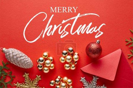 Photo pour Vue de dessus de la décoration brillante de Noël, enveloppe et thuja sur fond rouge avec illustration Joyeux Noël - image libre de droit