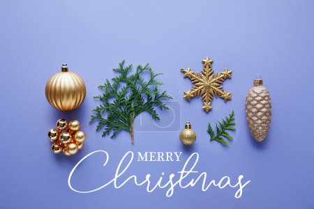 Photo for Top view of shiny golden Christmas decoration, green thuja branches on blue background with Merry Christmas illustration - Royalty Free Image