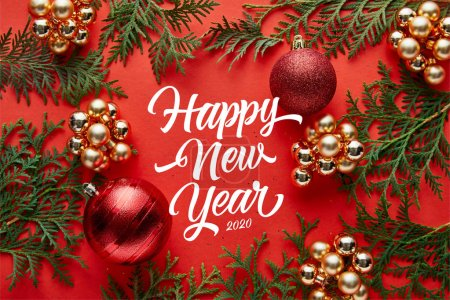 Photo pour Vue du dessus de la décoration de Noël brillante et thuja sur fond rouge avec un lettrage heureux nouvelle année - image libre de droit
