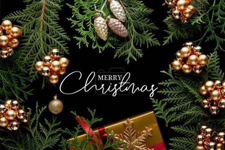 Photo pour Vue du dessus de la décoration de Noël dorée brillante, branches de thuja vert et boîte cadeau isolé sur noir avec illustration Joyeux Noël - image libre de droit