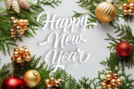 frame of shiny golden and red Christmas decoration on green thuja branches isolated on white with happy new year lettering