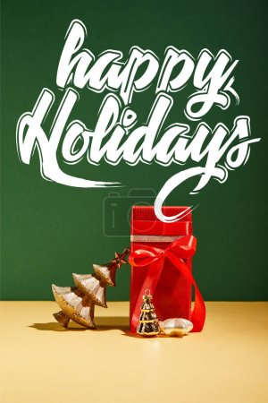 red gift box and decorative Christmas tree with golden baubles on green background with white happy holidays lettering