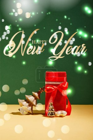 red gift box and decorative Christmas tree with golden baubles on green background with happy new year lettering