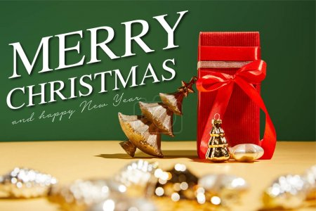 selective focus of red gift box and decorative Christmas tree with golden baubles on green background with Merry Christmas and happy new year illustration