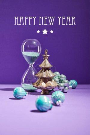 Foto de Selectivo foco de Navidad decorativa cerca de los tobillos azules y el reloj de noche en fondo púrpura con feliz carta de Año Nuevo. - Imagen libre de derechos
